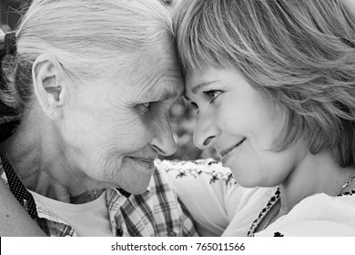 Middle-aged woman hugging her mother in nature. The real emotions of happiness. Mothers Day. Black and white photo.
