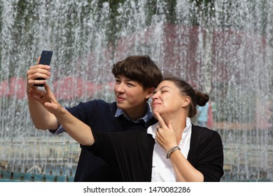 Middle-aged woman, mother, and teenager, son take a selfie at the fountain in the city park. Family resting together on the weekend.