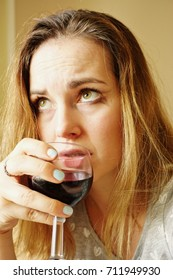 Middle-aged woman, in poor condition, with a glass of red wine in her hand.