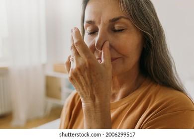 Middle-aged woman practicing yoga breathing technics at home. Elderly female breathing with one nostril. Surya bheda pranayama concept. Meditation idea