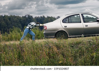 Middle-aged woman pushing her car which has run out of petrol along a country road using a tow rope. The strong woman exerts all his strength to pull the car