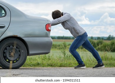 Middle-aged woman pushing her car which has run out of petrol along a country road. The strong woman exerts all his strength to pull the car