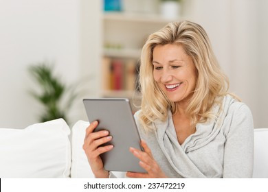 Middle-aged woman reading a message, e-book or information on her tablet computer with a look of excited anticipation as she sits on a couch at home