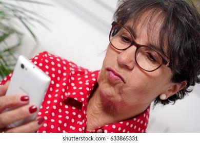 Middle-aged woman reading a text message on her mobile phone