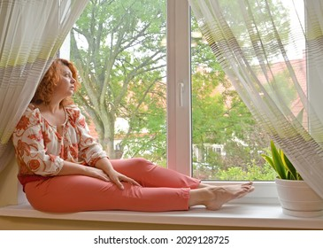 A middle-aged woman sits on the windowsill and looks thoughtfully out the window