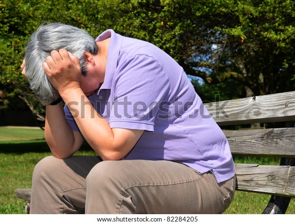 Middle-aged woman sitting on bench, head in hand in despair