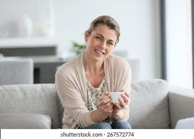 Middle-aged woman sitting in sofa, holding cup of coffee