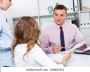 Middle-aged woman and son having consultation with college teacher
