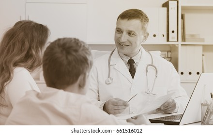 Middle-aged woman and son having consultation with male doctor in hospital