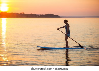 A middle-aged woman stand up paddle boards on a bay at sunset in Ontario, Canada.
