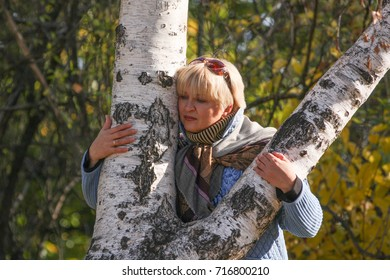 middle-aged woman standing near the autumn birches