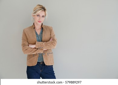 Middle-aged woman standing on grey background, isolated