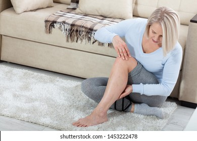 Middle-aged woman suffering from pain in leg at home, closeup. Physical injury concept. Ankle pain, painful point.