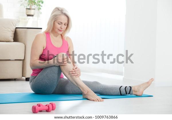 Frau mittleren Alters, die zu Hause an Beinschmerzen leidet, Nahaufnahme. Physikalisches Verletzungskonzept.