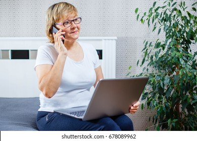 A middle-aged woman talking on the phone and working on laptop at home