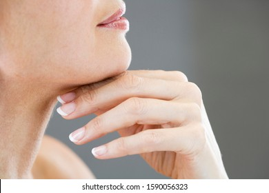 A middle-aged woman touching her neck