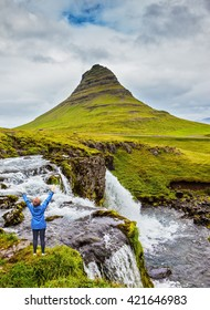 Middle-aged woman tourist admires the beauty of nature. Threaded full-flowing waterfall Kirkjufell Foss on the grassy mountains