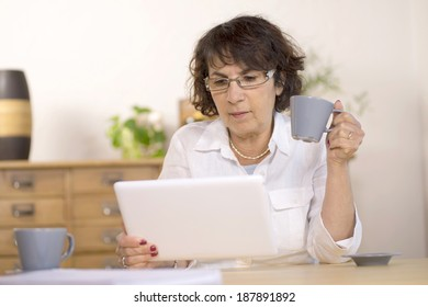 a middle-aged woman using a  computer tablet in her kitchen
