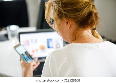 Middle-aged woman using phone and laptop at home