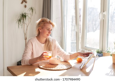 Middle-aged woman using tablet in kitchen