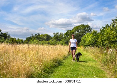 Middle-aged woman walking her dog on a summer afternoon