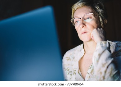 Middle-aged woman working on laptop in dark room
