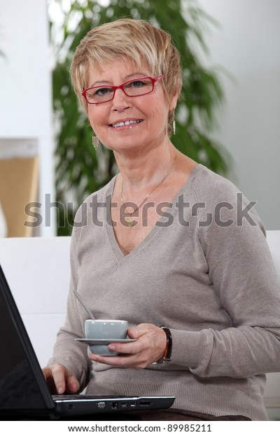 Middle-aged women drinking coffee whilst surfing the internet
