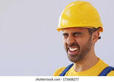 Middle-aged workman wearing a safety helmet or hardhat screwing up his eyes in pain due to a migraine headache or injury over a grey studio background with copyspace