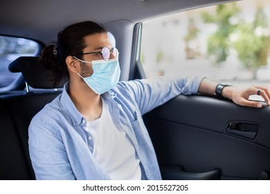 Middle-eastern young man in protective face mask and glasses sitting in taxi, looking through window at copy space, indian guy using cab while coronavirus pandemic, sitting at backseat