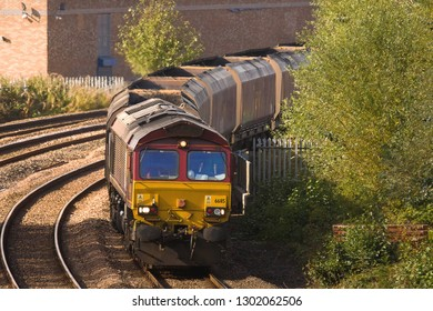 MIDDLESBROUGH, NORTH YORKSHIRE, UK - OCTOBER 9, 2012: EWS liveried DB Schenker Class 66 No. 66115 hauls a train of loaded coal hoppers through Middlesbrough to the nearby Teeside Steelworks.
