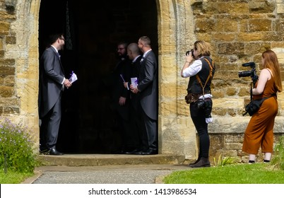 Middleton Cheney, Northamptonshire. England- June,1. 2019: Wedding photographers at work at the doorway of All Saints Church, with male ushers at a wedding whilst waiting for the bride to arrive.
