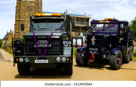 Middleton Cheney, Northamptonshire. England- June1, 2019: Two vintage Scammell trucks, purple ribboned and used to bring the bride and attendants to All Saints Church on her Wedding Day.
