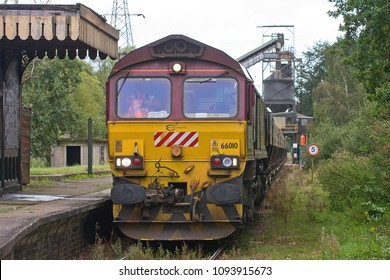 MIDDLETON, NORFOLK, UK - SEPTEMBER 14, 2012: Euro Cargo Rail-liveried DBS Class 66 No. 66010 departs Middleton Towers, with a train of loaded hoppers, a cargo of fine sand for a glassworks in Goole.