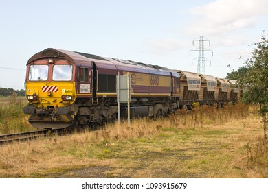 MIDDLETON, NORFOLK, UK - SEPTEMBER 14, 2012: Euro Cargo Rail-liveried DBS Class 66 No. 66010 approaches Middleton Towers with a train of sand hoppers, to load a cargo of sand, for glass work at Goole.