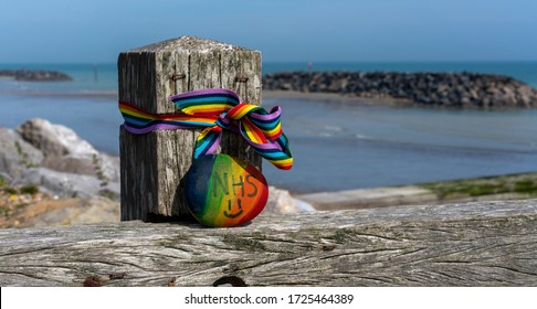 Middleton on Sea, Sussex / UK - 7 May 2020: Seaside wooden post decorated with a rainbow ribbon and painted beach pebble with the letters NHS - during the Covid-19 pandemic. The rocks at Elmer beyond.