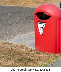 Middleton on Sea, West Sussex / UK - July 28 2018: Bright red bin designated for the disposal of dog faeces is strategically placed near a popular pet walking area.