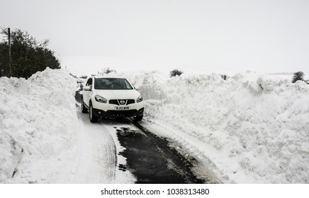 MIDDLETON, SCOTLAND - MARCH 4: a car drives between deep banks of snow on March 4, 2018 in Middleton, Scotland. Central Scotland experienced its most significant snowfall since 2010 in Feb-Mar 2018.