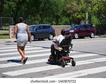 Middletown, CT USA. Jul 2019. African American mother escorting her son on a powered wheelchair at the crosswalk.