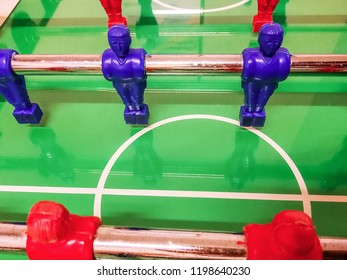 Midfielder of a red and blue football table in a game room