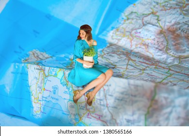 Midget woman in blue on the map. Travelling background.