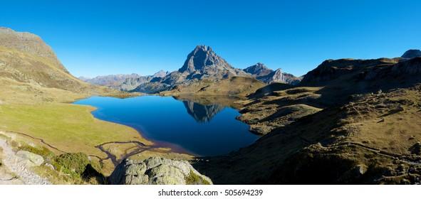 Midi Dossau Peak reflected in Gentau lake. Ossau Valley, Pyrenees National Park, Pyrenees, France.