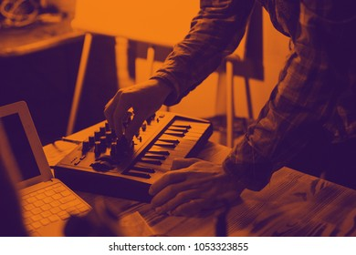 Midi keyboard and laptop - the process of recording sound and music. Duotone effect - orange and purple colors