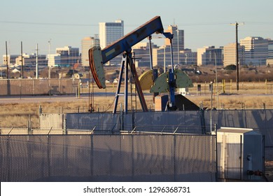 Midland, Texas - January 27, 2019: Pumpjack with Downtown Midland in Background