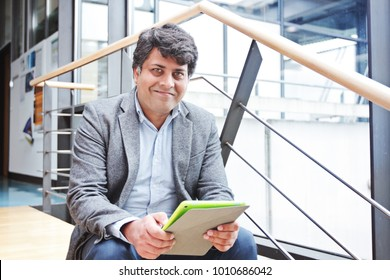 Midle aged indian businessman with tablet