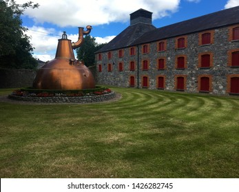 Midleton, County Cork / Ireland - June 24 2017 : Lawn and copper still outside the Jameson Distillery