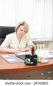 Mid-life business woman sign document in office