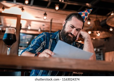 Midlife crisis. Dark-haired man feeling unhappy while overcoming midlife crisis sitting in bar