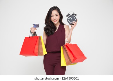 Midnight sale, Portrait of a happy young women in red dress holding shopping bags and black alarm clock, Year end sale or mid year sale promotion clearance for Shopaholic concept, Asian female model
