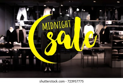 midnight sale text with blur clothing shop in night.For background idea