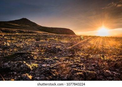 Midnight sun on a polar day in the mountains near Nordkapp, Norway, with sun flare and sunlit tundra vegetation and rocks